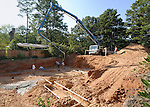 A crew of Latino workers uses a concrete pump and boom-arm to fill the footings of a new house as the pump operator looks on.  The house is being built on the lot from a 'tear-down' home project in an established North Atlanta neighborhood.  A new 'McMansion' will take its place.