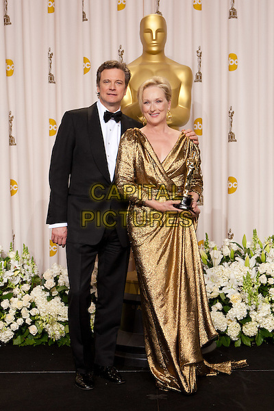 """Colin Firth and Oscar®-winning actress Meryl Streep, winner for Performance by an Actress in a Leading Role for her role in """"The Iron Lady"""", pose backstage. The 84th Annual Academy Awards® are broadcast live on the ABC Television Network from the Hollywood and Highland Center, in Hollywood, CA, Sunday, February 26, 2012..*Editorial Use Only*.oscars award trophy winner full length gold dress black tuxedo.CAP/A.M.P.A.S./NFS.©A.M.P.A.S. Supplied by Capital Pictures."""