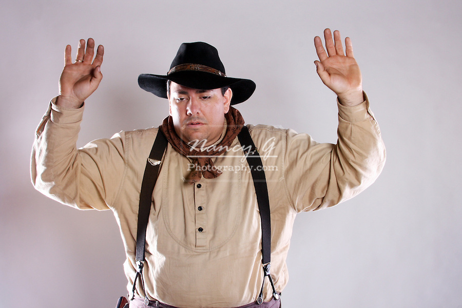 A cowboy raising his hands under arrest