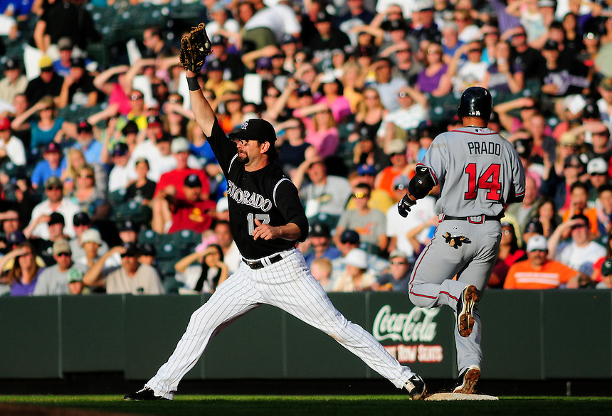 July 9, 2009: Rockies 1st baseman Todd Helton stretches for the ball at 1st base while Braves 3rd baseman Martin Prado crosses the bag during a regular season game between the Atlanta Braves and the Colorado Rockies at Coors Field in Denver, Colorado.