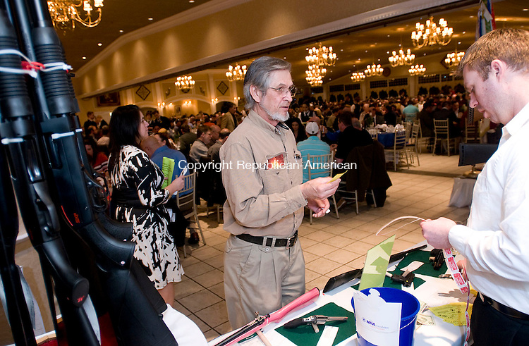 SOUTHINGTON, CT 18 MARCH 2011--031811JS11---<br /> Andy Chernok of Seymour, left, buys raffle tickets from volunteer Joe Charette of Southington, right, during the 18th annual Nutmeg Friends of the National Rifle Association banquet Friday at the Aqua Turf in Southington. More than 1400 supporters turned out for the event. All proceeds from the event is put back into the state organization. <br /> Jim Shannon/Republican-American