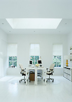 A twin study with facing desks is located in a light upstairs room that has been painted white throughout