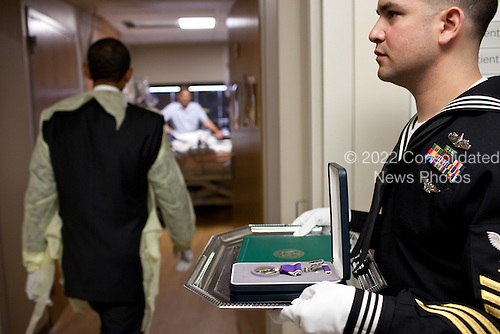 United States President Barack Obama visits a wounded warrior for a Purple Heart presentation at Walter Reed National Military Medical Center in Bethesda, Maryland, October 10, 2011..Mandatory Credit: Pete Souza - White House via CNP