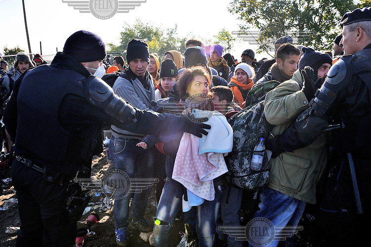 A woman with her baby and baggage is moved along by a police officer amongst a surge of refugees and migrants attempting to cross the Serbian-Croatian border at Berkasovo / Bapska. The Croatian authorities had attempted to control the flow of people by holding them at the frontier until transport was available for them to be taken the 12 kilometers to be registered at the Opatovac Transit Centre. Some people however went around the police, across fields. /Felix Features