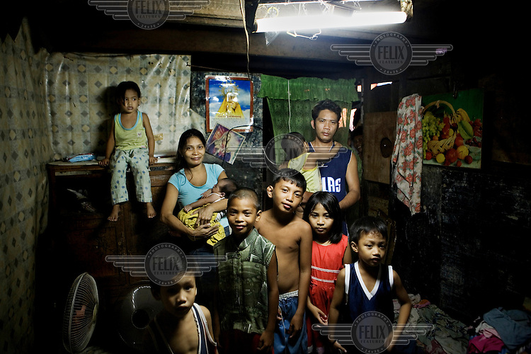 The Esponilla family in their house in Santo Nino, Manila. Bhona and Charito Esponilla have around 20 square meters of space to share with their children. People in this area live in small homemade huts, many made entirely from rubbish and leftover building materials that they found on the nearby garbage dump. These houses are all illegal, since no one has the acquired permissions to live on the land. People have been living here for up to twenty years - but everyday they might get moved and their neighbourhood demolished to make room for new apartment blocks that they could never afford to buy.
