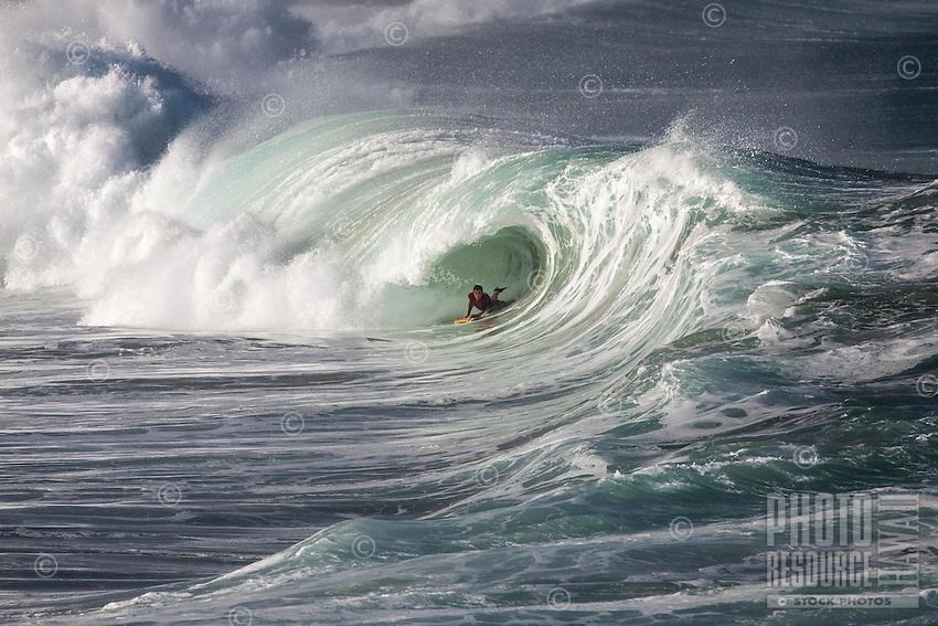 A bodyboarder rides a big hollow wave at Waimea Shorebreak, North Shore, O'ahu.