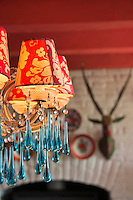 A chandelier in the living room features hand-blown crystal drops and red patterned lampshades