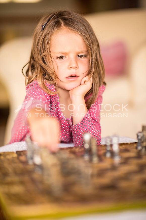 Young girl (5 years) concentrating and playing chess, New Zealand - stock photo, canvas, fine art print