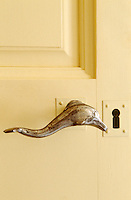 A detail illustrating a silver doorknob in the shape of a dolphin on the living room door