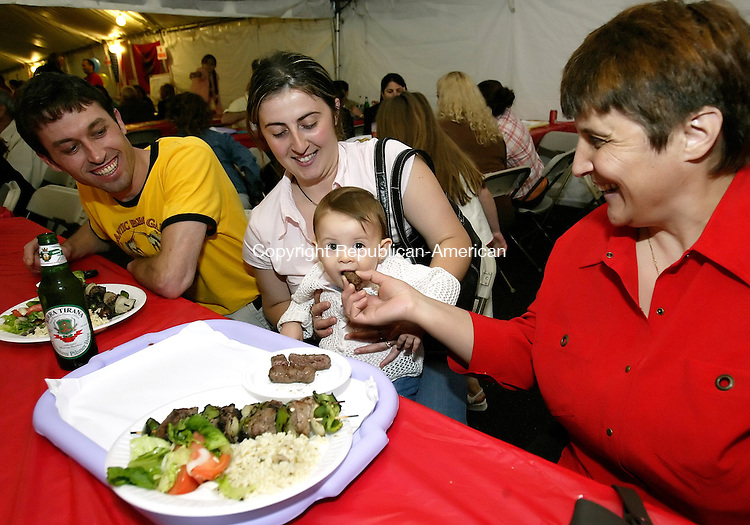 WATERBURY, CT, 03 June 2006- 060306BZ08- Roland Strumi, of Waterbury, and his wife , Manuela Strumi, watch as their daughter Alexia Strumi, 11-months-old, is fed Albanian sausage by Manuela's mother, Rezina Hasimillari, of Waterbury, during the first Albanian Festival at the Albanian-American Moslem Community of Waterbury Saturday.  <br /> Jamison C. Bazinet Republican-American