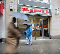 People walk by a Sleepy's mattress store in New York on Tuesday, December 1, 2015. Mattress Firm announced it is acquiring Sleepy's in a $780 million deal. Mattress Firm is acquiring Sleepy's 1050 stores in addition to its existing 2420 locations and will operate both brands, at least for now. (© Richard B. Levine)