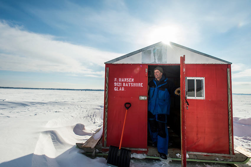 "An ice fisherman looks out from a larger ""sleeper"" ice fishing shelter featuring bunks for sleeping in on Little Bay de Noc near Gladstone, Michigan."