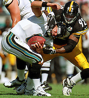 Jacksonville Jaguars quarterback #8 Mark Brunell nearly has his head taken off by Pittsburgh Steelers linebacker #92 Jason Gildon as Gildon twists Brunell's face mask while sacking him.