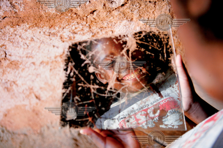 A girl orphaned by AIDS looks into a scratched mirror.