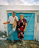 GREECE, Patmos, Diakofti, Dodecanese Island, portrait of Mihalis with his lyra and Katerina Grillakis at their restaurant, Diakofti Taverna