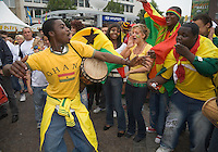 Germany, DEU, Dortmund, 2006-Jun-27: FIFA football world cup (USA: soccer world cup) 2006 in Germany; black and white Ghanaian football fans making music at a public viewing zone on the Friedensplatz before the world cup match Brazil vs. Ghana (3:0).