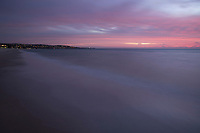 A bright pink sunset fades above the coast at Adelaide, South Australia, looking south towards Brighton Seacliff and Marino Rocks.