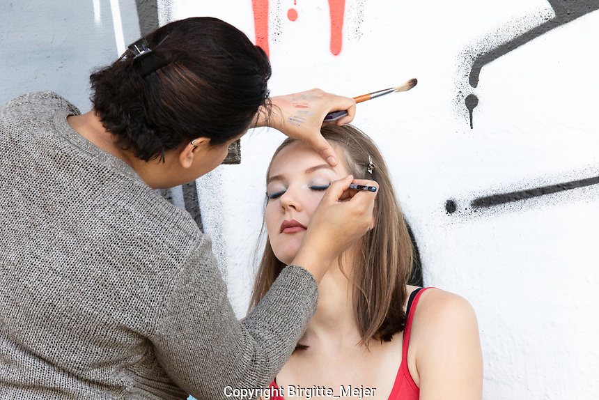 Model having make-up put on by make-up artist, background white and red concrete wall