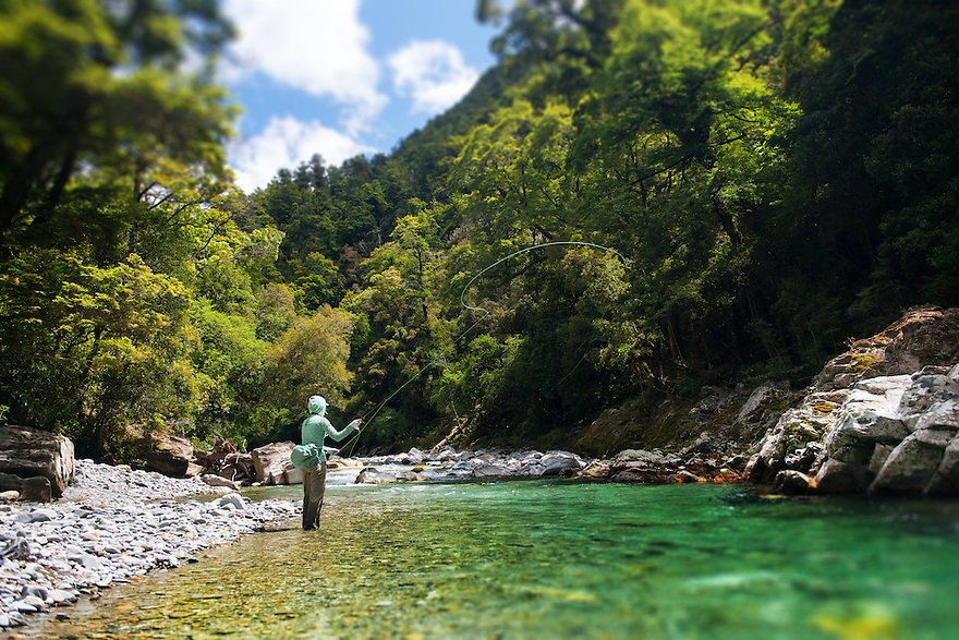 A fly fisher wades in emerald waters in Kahurangi National Park, South Island, New Zealand.