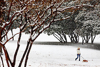 A woman and dog walk during a January snowstorm in Charlotte, North Carolina.