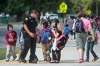 NWA Democrat-Gazette/ANTHONY REYES &bull; @NWATONYR<br /> Eric Cardenas, school resource officer, greets children Thursday, Sept. 10, 2015 outside of Jones Elementary School in Springdale. Cardenas talks with the children and helps keep traffic steady, smooth and safe for the children. Overall crime rates are down or stable in northwest Arkansas including Springdale.