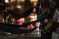 May 23, 2016 - Kampong Khleang, Cambodia. Cham som's (58) grand-daughter lays in a hammock in the family home. A few years ago the family invested in shrimp traps through a micro finance loan, three years later fish stocks in the lake are so low that they are unable to repay their loan and their investment sits idol under the family home. © Nicolas Axelrod / Ruom