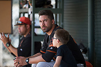 San Francisco Giants Orange coach Travis Ishikawa sits with his son in the dugout during an Extended Spring Training game against the Oakland Athletics at the Lew Wolff Training Complex on May 29, 2018 in Mesa, Arizona. (Zachary Lucy/Four Seam Images)