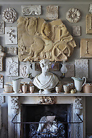 The delicate pottery arranged on the mantelpiece around a classical bust continues up the surrounding walls into an imposing collection of architectural casts