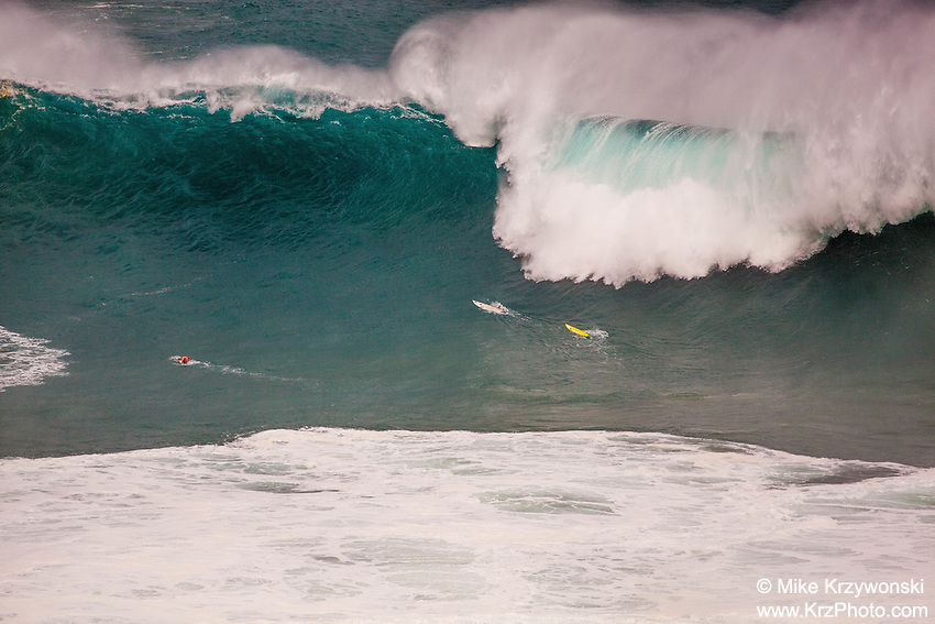 Surfers caught inside of a giant breaking wave at the 2016 Big Wave Eddie Aikau Contest, Waimea Bay, North Shore, Oahu