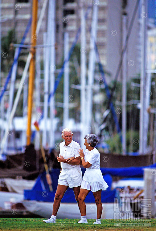 A handsome silver haired older couple wearing white tennis clothes walk briskly by sailboats moored at the Ala Wai Yacht harbor in Honolulu.