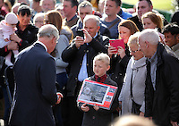 Pictured: Prince Charles speaks to a young boy with an album with pictures from the time at the Memorial Garden in Aberfan Friday 21 October 2016<br />