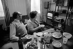 Jewish family at home north London watching TV in their dinning room cum living room. 1970s UK. The table has been laid out for an evening meal and is now al but over. The Goodman family at home, Mr David,  Goodman, always known a Lou, was a taxi driver based in Manor House, 1970s UK.