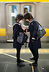 (Eng) Tokyo, 8th of November 2009 - Two High school students watching a mobile phone on a train station plateform.<br /> <br /> (Fr)Tokyo, 9 novembre 2009 - Deux collegiennes rient en consultant un telephone portable dans le metro.