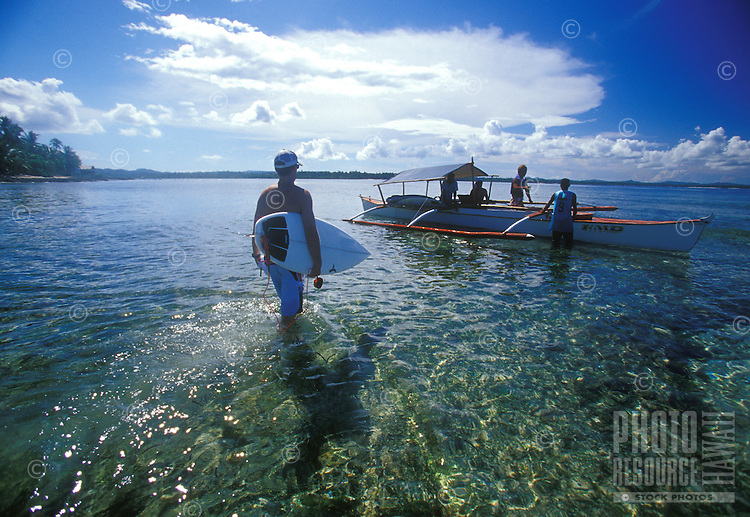 Surfers heading out in an outrigger canoe in clear water, Philippines