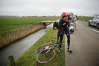 Lars Bak (DEN/Lotto-Soudal), holding onto his bike to prevent it from flying into the ditch beneath, after crashing out of the peloton due to the extreme winds in De Moeren (up to 80km/h).<br /> <br /> 77th Gent-Wevelgem 2015