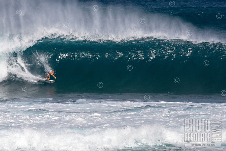 A surfer gets barreled  on a big wave at Pipeline (off of 'Ehukai Beach Park), North Shore, O'ahu.