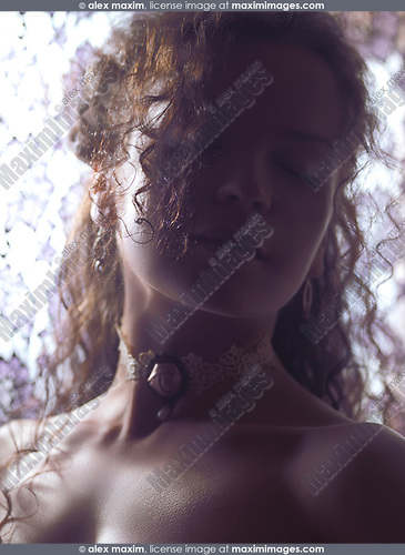 Artistic beauty portrait of a young woman sensual face with closed eyes lit by soft sunlight coming from a window