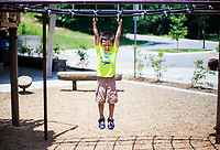 NWA Democrat-Gazette/CHARLIE KAIJO Royce Katt, 4, of Rogers hangs from a jungle gym during a hot day, Monday, July 2, 2018 at Lake Atalanta Park in Rogers.