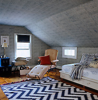 A blue and white dhurrie on the floor of this child's bedroom complements the fabric on the walls and ceiling