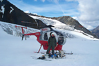 Ron Karpilo with a steam drill and glacier mass balance monitoring equipment standing front of a 1977 Hughs 369D helicopter on East Fork Toklat Glacier, Denali National Park and Preserve, Alaska, United States.