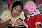 Christian Love Daroy-Gagno, the program director of the Kapatiran-Kaunlaran Foundation (KKFI), helps a girl learn about the letter N in a KKFI-sponsored preschool in Pulilan, a village in Bulacan, Philippines.<br /> <br /> KKFI is supported by United Methodist Women.