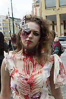 woman participating in the zombie walk in prague 2014. Wering a white dress, with blood on it, and a crown that is supposed to look as if it has damaged her right eye. Looking straight at the Camera.
