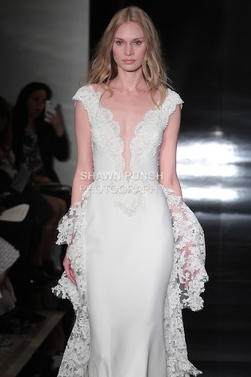 Model walks runway in a silk georgette gown with plunging neckline and re-embroidered lace bodice, from the Reem Acra Spring 2017 bridal collection, during New York Bridal Fashion Week Spring Summer 2017, on April 15, 2016.