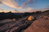 Tent pitched on rocky terrain near summit of Moldtind mountain peak, Moskenesøy, Lofoten Islands, Norway