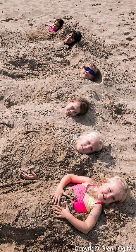 Keeping the kids busy at Mike Weir Park beach is a cover-up. Lined up like hot dogs in a pack are from; background to foreground; Adele, 5 and Eligah Miranda, 8, Lincoln Kleinsmith, 5, Skye Roscoe-Stevenson, 4, Reese , 5 and Anna Lavoie, 3. The kids were covered with sand by their moms.