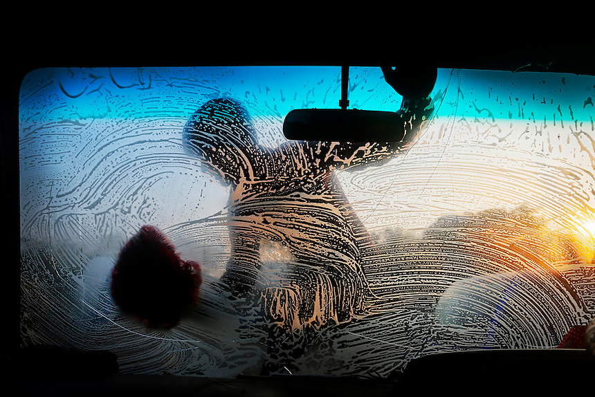 A Bangladeshi boy cleans the front glass of a car early morning in Dhaka, Bangladesh.