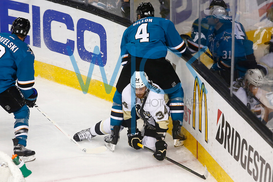 Tom Kuhnhackl #34 of the Pittsburgh Penguins is sat on in the corner by Brenden Dillon #4 of the San Jose Sharks in the second period during game four of the Stanley Cup Final at the SAP Center in San Jose, California on June 6, 2016. (Photo by Jared Wickerham / DKPS)