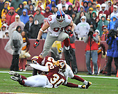 Landover, MD - November 30, 2008 -- New York Giants tight end leaps over Washington Redskins defenders LaRon Landry (30) and Carlos Rogers (22) after a first quarter reception at FedEx Field in Landover, Maryland on Sunday, November 30, 2008..Credit: Ron Sachs / CNP.(RESTRICTION: No New York Metro or other Newspapers within a 75 mile radius of New York City)