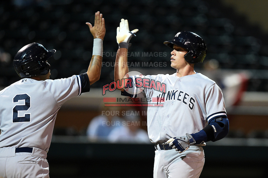 Tampa Yankees shortstop Cito Culver (2) high fives catcher Peter O'Brien (24) after a home run during a game against the Lakeland Flying Tigers on April 3, 2014 at Joker Marchant Stadium in Lakeland, Florida.  Tampa defeated Lakeland 4-0.  (Mike Janes/Four Seam Images)