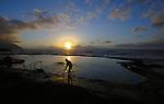 Silouhette of man entering  sea pool as sun sets over playa del Piloto, El Hierro, Canary Islands.